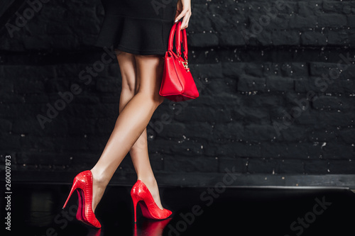 Valokuvatapetti Photo of sexy, women's legs in red shoes on a black  background