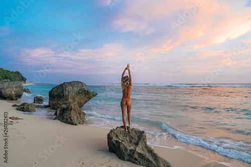 Canvas Print European attractive girl in brown bathing suit standing on rocky beach during su