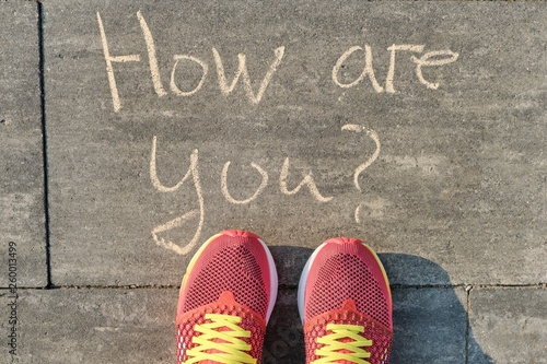 Photo How are you? written on gray sidewalk with womens legs in sneakers, top view