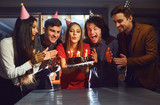 Friends blowing birthday candles on the cake indoors - 260015408