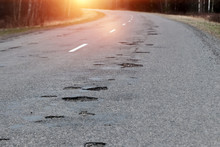 The Road In Disrepair With A Lot Of Potholes. Cars Go With The Risk Of Breakdowns.