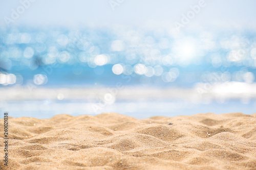 Fototapeta Seascape abstract beach background. blur bokeh light of calm sea and sky. Focus on sand foreground. obraz