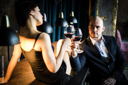 Fényképezés  A man in a black suit sitting at the bar, next to him sitting on the bar dark-haired girl in a black dress, they are minted glasses of red wine