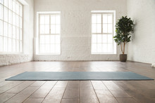 Unrolled Yoga Mat On Wooden Floor In Yoga Studio
