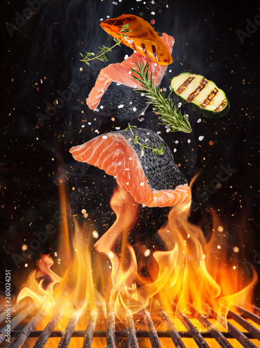 Fotografia Tasty salmon steaks flying above cast iron grate with fire flames