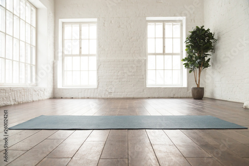 Fototapeta Unrolled yoga mat on wooden floor in yoga studio