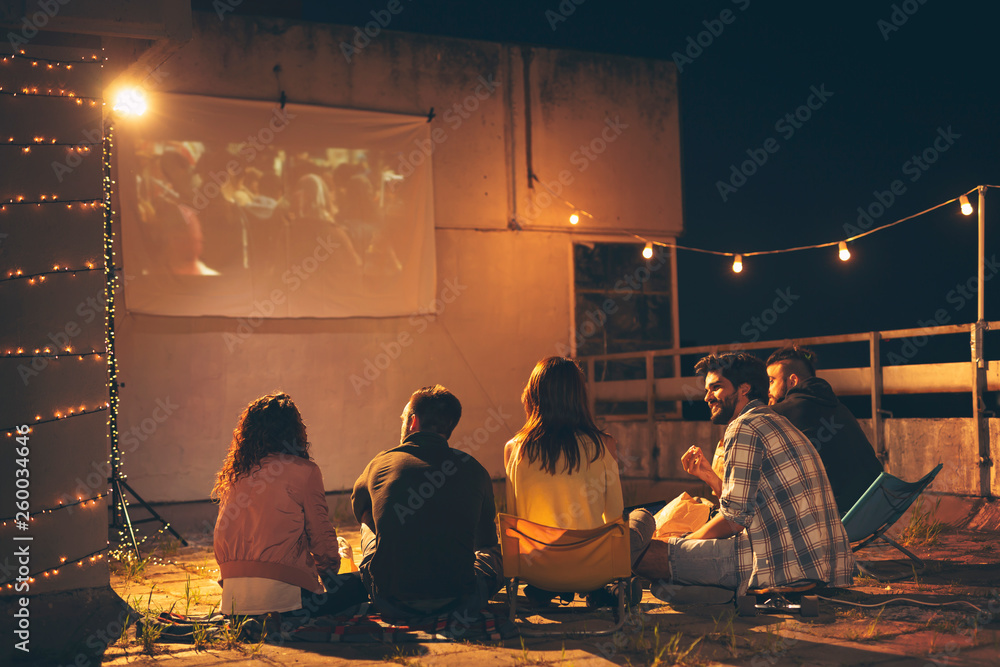 Fototapety, obrazy: Friends watching a movie on a building rooftop terrace