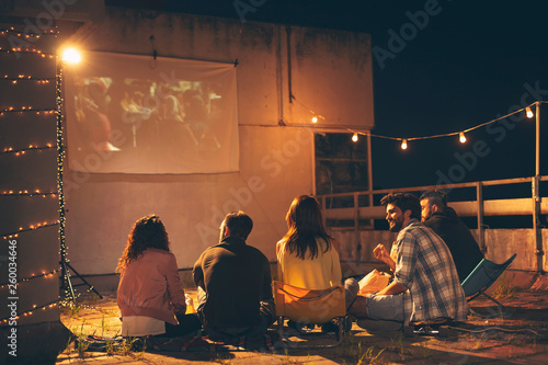 Fotografiet  Friends watching a movie on a building rooftop terrace