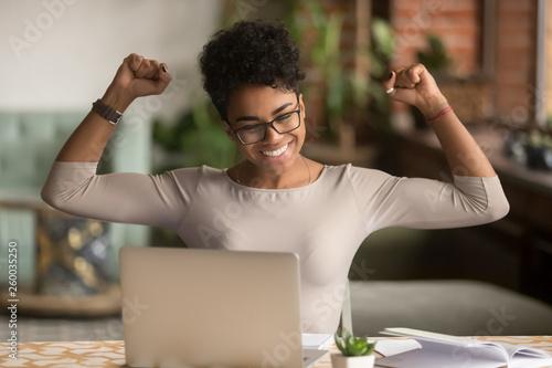 Foto Excited african woman feeling winner rejoicing online win on laptop