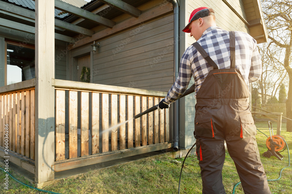 Fototapety, obrazy: Man cleaning terrace with a power washer - high water pressure cleaner on wooden terrace railing