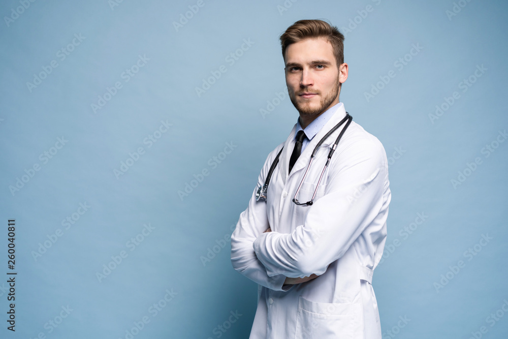 Fototapety, obrazy: Portrait of confident young medical doctor on blue background.