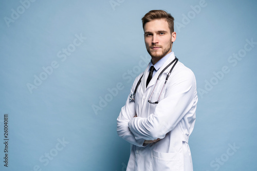 Carta da parati  Portrait of confident young medical doctor on blue background.