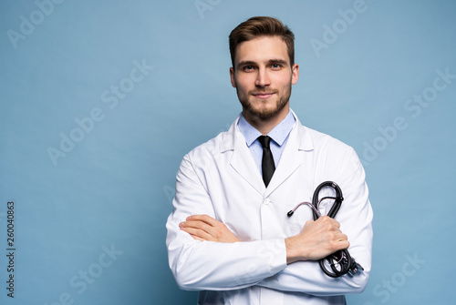 Cuadros en Lienzo Portrait of confident young medical doctor on blue background.