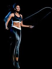 jeden piękny kaukaski kobieta rasy mieszanej ćwiczenia ćwiczenia fitness skakanka w studio na białym tle na czarnym tle