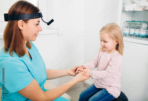 Fotografia  Cheerful pediatrician playing with her little patient's