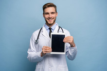 Portrait Of Friendly Doctor Presenting Empty Digital Tablet Screen. Isolated On Light Blue.
