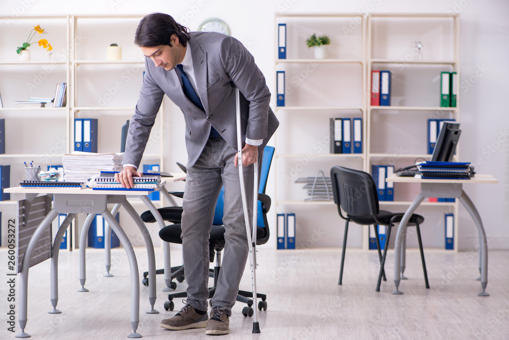Leg injured male employee working in the office