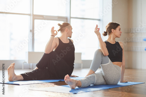 Montage in der Fensternische Yoga schule Serious young couple sitting on exercise mats and twisting bodies while making marichis pose to strengthen spine