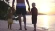 The young father holds his children's hands and walks with them along the beach
