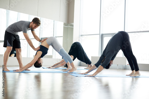 Valokuva  Content handsome young qualified yoga coach assisting students at class: he corr