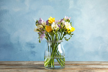 Bouquet Of Fresh Freesia Flowers In Glass Vase On Table
