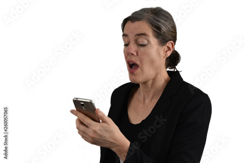 Photo Attractive middle-aged woman with graying hair looks surprised with open mouth on her phone