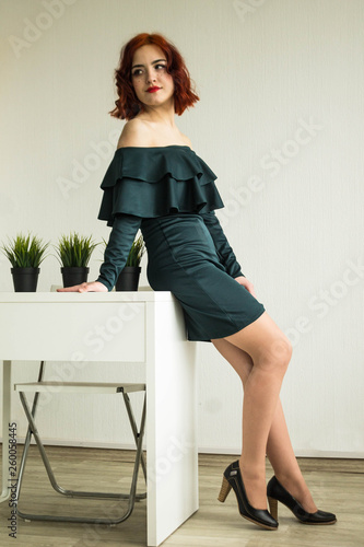 Fotografía  Beautiful red-haired girl in a green dress at the table