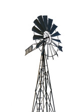 Low Angle View Of An Old-fashioned, Multi-bladed, Metal Wind Pump Atop A Lattice Tower In Backlight, Isolated On White Background.