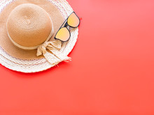 Summer Concept From Sunglasses And Straw Beach Hat, Flat Lay On Red Background Pastel Color For Advertising Sale Products.