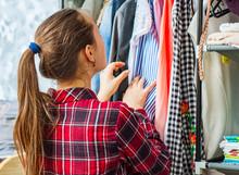 Teenage Girl Choosing Clothes From Wardrobe