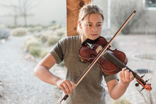12 Year Old Girl Playing Violin Under Portal In Rural Setting