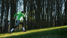 Side View Of An Athlete Young Man Running On A Hill In Mountain. Athletic Male Jogging In The Park In The Morning In A Sunny Day. People, Healthy Lifestyle And Sport Concept