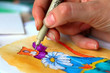 A woman's hand holds a pen and draws a picture with funny cat. Creative hobby. Painting for beginners. Novice artist. Art idea. Closeup, selective focus