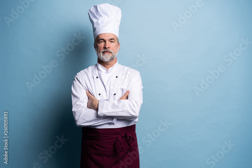 Fotografie, Obraz  Attractive smiling cheerful chef isolated on blue.