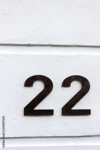 Fotografia  Stark and simple - house number 22 with the twenty-two in black on a white wall