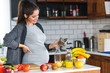 Leinwanddruck Bild - Beautiful smiling young pregnant woman preparing healthy food with lots of fruit and vegetables at home kitchen