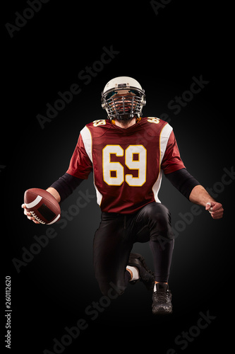 Fotografía  Portrait of American football player holding a ball with both his hands