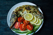 Baked pike in the oven, decorated with vegetables and herbs. Serving on a plate. Proper nutrition. Dark wood background.