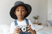 People, Photography, Art And Hobby Concept. Indoor Image Of Cute Adorable Afro American Boy Posing In Cozy Bedroom Interior Wearing Stylish Round Hat, Holding Vintage Camera, Taking Pictures