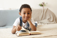 Curious Handsome Cute African Schoolboy Reading Book On Floor In Living Room. Adorable Black Male Child Spending Nice Time Indoors With Interesting Book, Lying On Carpet, Looking At Camera With Smile