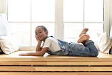 Relaxation, Leisure, People And Lifestyle Concept. Portrait Of Confident Handsome African American Little Boy Lying On His Stomach On Wooden Windowsill, Raising His Bare Feet, Looking At Camera