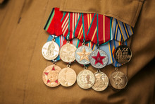 USSR And Russia Veteran Soldier Medals Of War In Afghanistan And WWII. Close Up World War Veteran Military Service Ribbons And Medals Of Honor On The Jacket Of The Veteran. Victory Day Celebration.