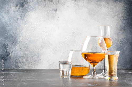 Keuken foto achterwand Alcohol Set of hard strong alcoholic drinks and spirits in glasses in assortment: vodka, cognac, tequila, brandy and whiskey, grappa, liqueur, vermouth, tincture, rum. Gray bar counter