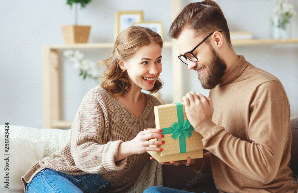 Fototapeta Happy married couple man and woman give a gift for holiday