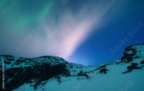 Poster Aurore polaire Aurora borealis above the snow covered mountain range in europe. Northern lights in winter. Night landscape with green polar lights and snowy mountains. Starry sky with aurora. Nature. Space