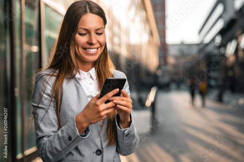 Pinturas sobre lienzo  Young smiling businesswoman using mobile phone outdoors