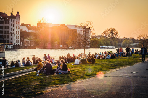 Foto People enjoying sunset at river next to the Berlin Wall / East Side Gallery  in