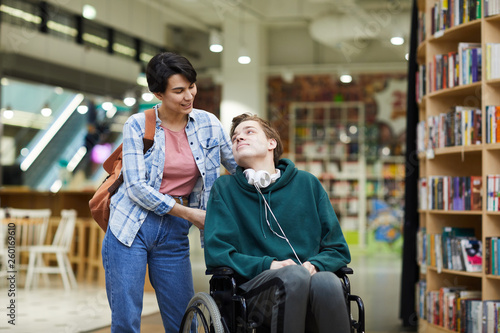 Obraz Positive attractive young woman with satchel pushing wheelchair and talking to disabled student in library - fototapety do salonu