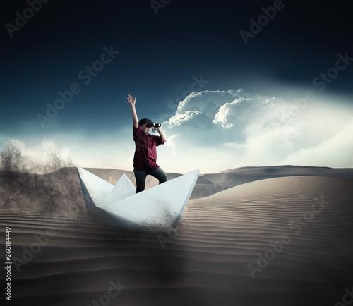 Photo  Navigate in the desert on paper boat