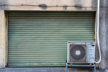 Grungy Weathered Metallic Roller Shutter Door With Old Air Conditioner Condensing Unit For Backgroud And Texture.